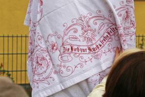 """Detail des Verhüllungstuches der Schadow-Stele mit der Aufschrift: """"Die Lieb`zur Kunst & frohe Feste"""""""